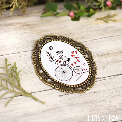 Bebé Lobito en bicicleta representado en un broche ilustrado.